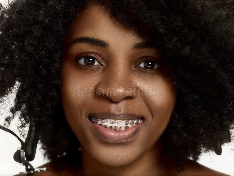 Портрет молодой чернокожей женщины усмехаясь с расчалками стоковое изображение rf