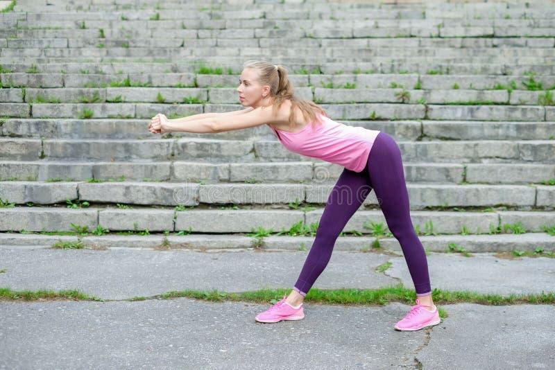 Портрет молодой sporty женщины в платье спорта делает протягивать тренировки внешние стоковое фото rf