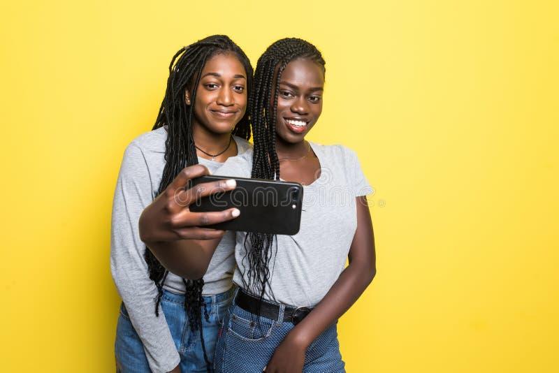Портрет 2 молодых африканских девушек усмехаясь и развевая рука на камере пока принимающ selfie на мобильном телефоне изолированн стоковое фото
