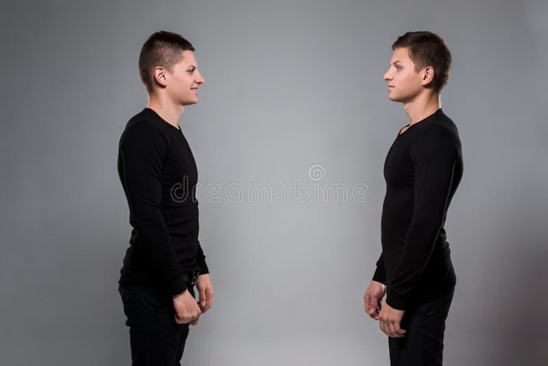 Портрет молодых брат-близнецов стоя лицом к лицу на сером ба стоковое изображение rf