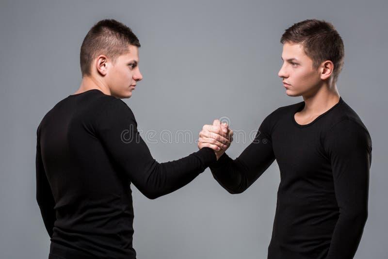 Портрет молодых брат-близнецов стоя лицом к лицу на сером ба стоковые изображения