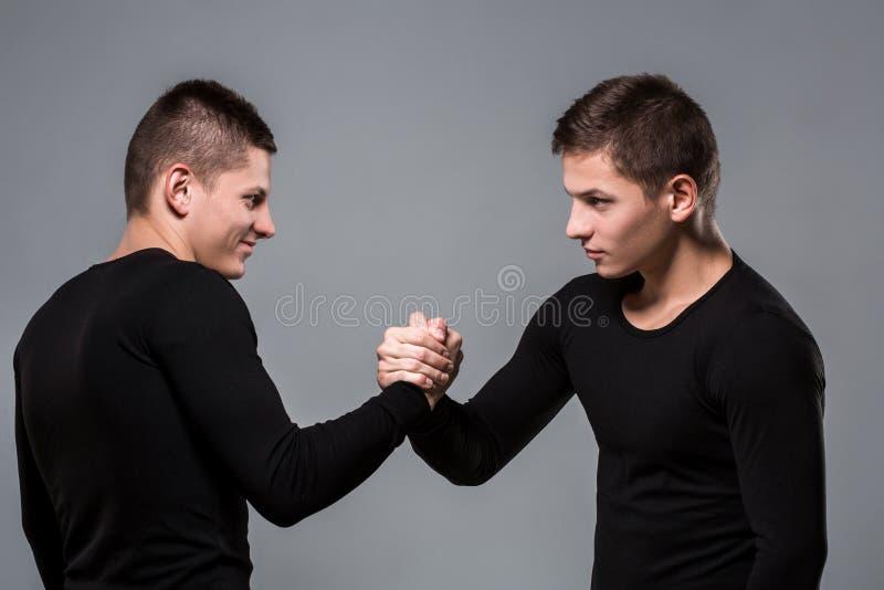 Портрет молодых брат-близнецов стоя лицом к лицу на сером ба стоковая фотография rf