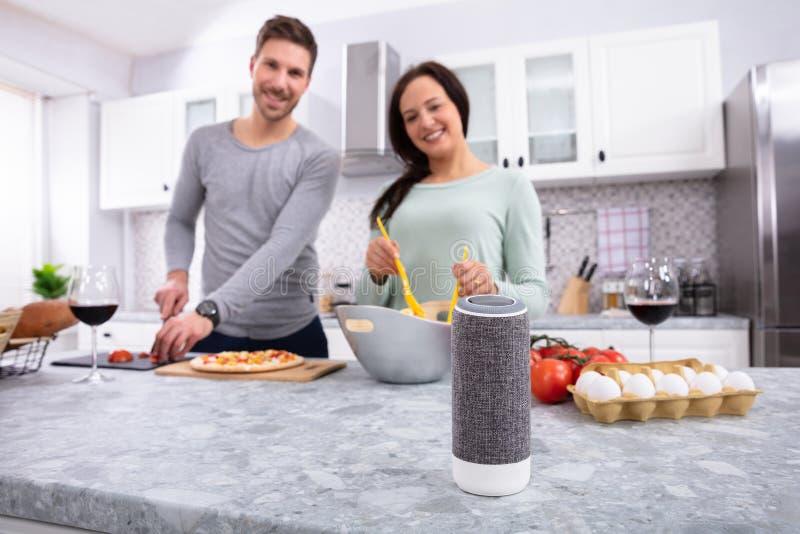 Портрет молодых пар подготавливая еду в кухне стоковое фото