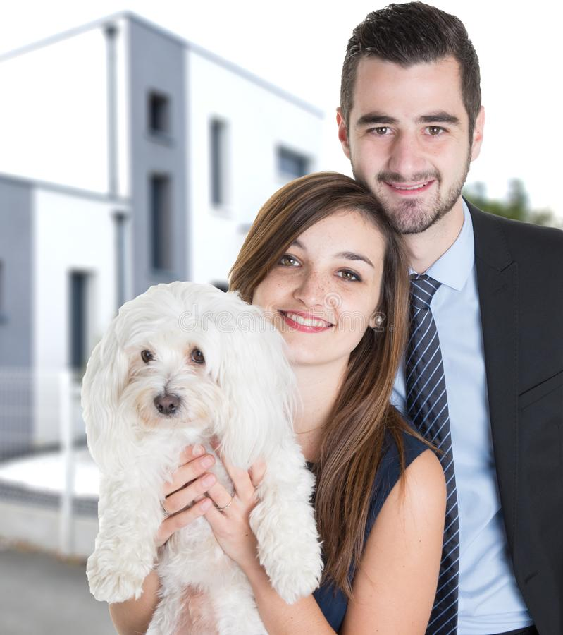 Портрет молодых пар с белой собакой рассматривая дом стиля архитектурного дизайна загородки заднего двора современный стоковые изображения rf