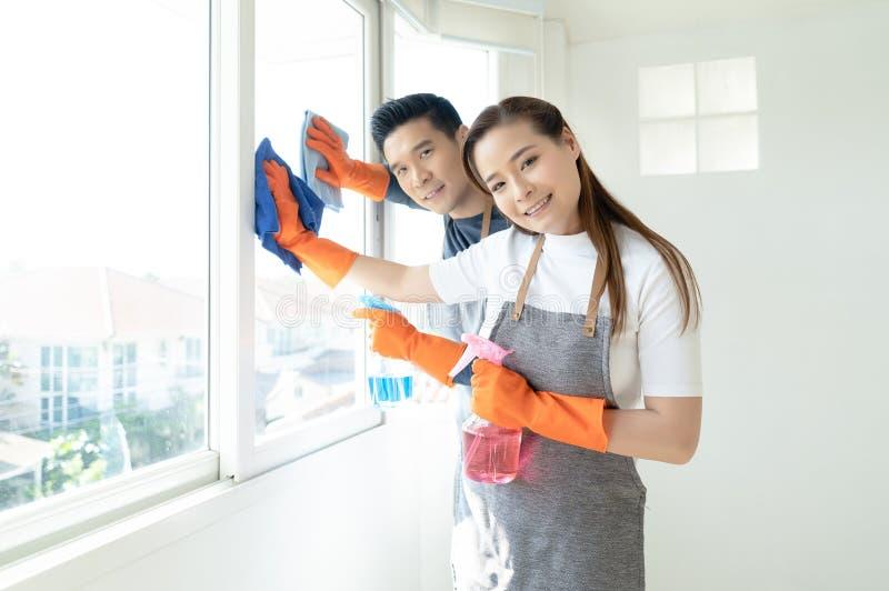 Портрет молодых счастливых азиатских пар пока делающ чистку и смотрящ камеру дома Люди, любовь, семья, отношения стоковая фотография