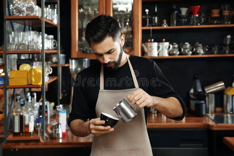 Портрет молока barista лить в чашку кофе против полок бара стоковое фото rf