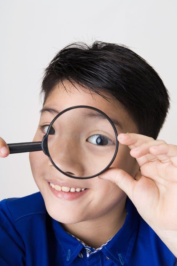 Портрет молодого азиатского ребенка смотря через увеличивая gla стоковое изображение