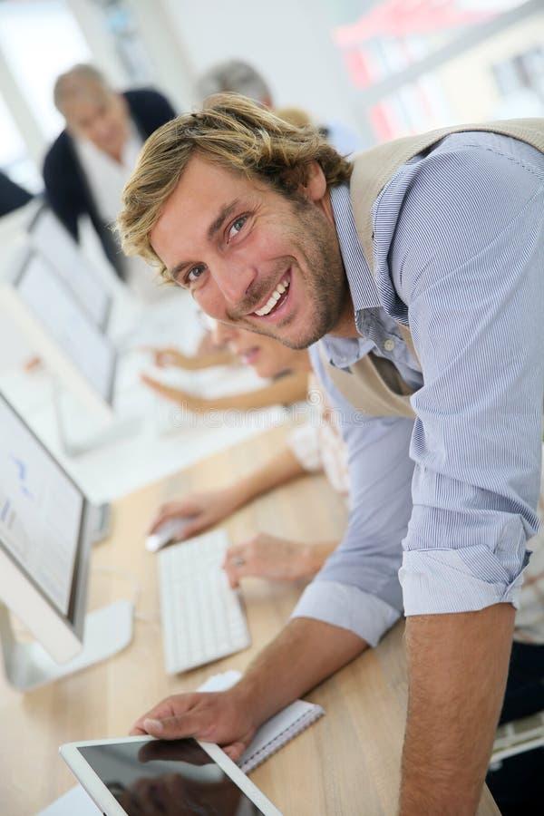 Портрет молодого инструктора в предпринимательском классе среди старшиев стоковые изображения