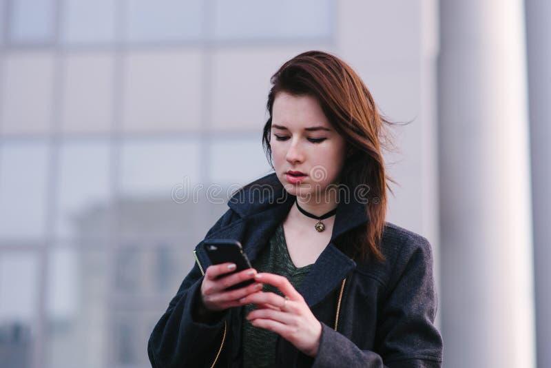 Портрет молодого красивого брюнет женщины в черноте, которая использует мобильный телефон на предпосылке света города стоковые изображения rf