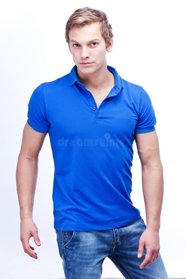 Портрет молодого красивого человека нося голубой t-короткий изолированный o стоковое изображение