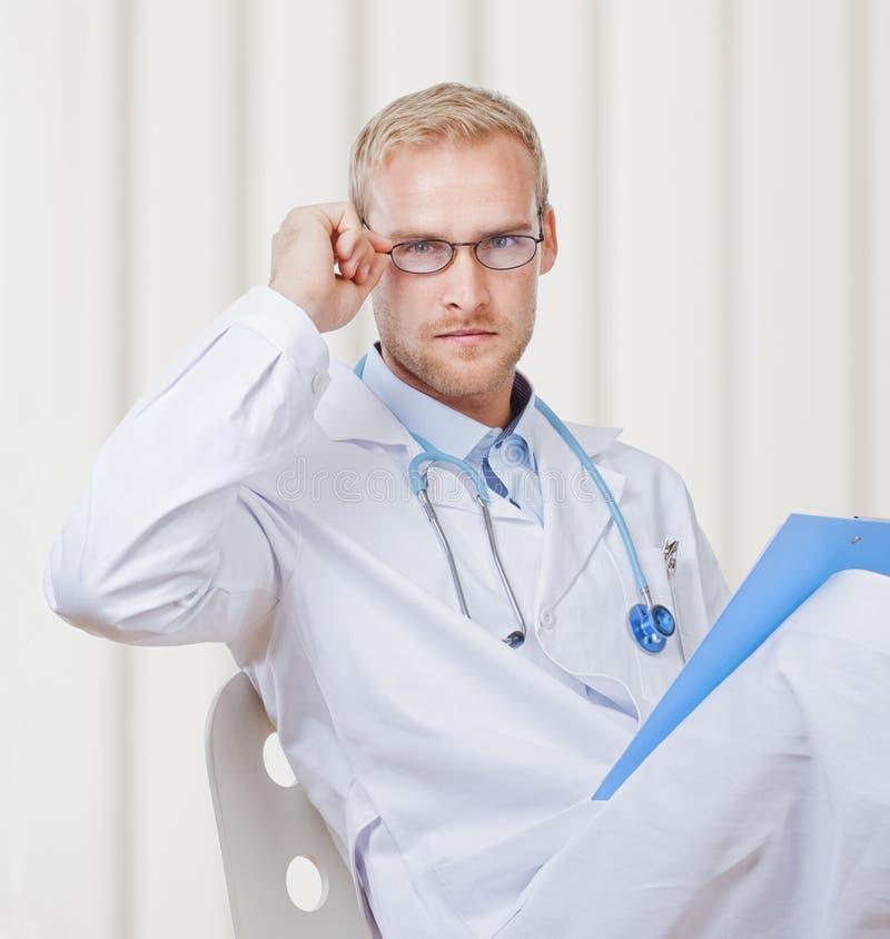 Портрет молодого доктора с стетоскопом и стеклами стоковое изображение