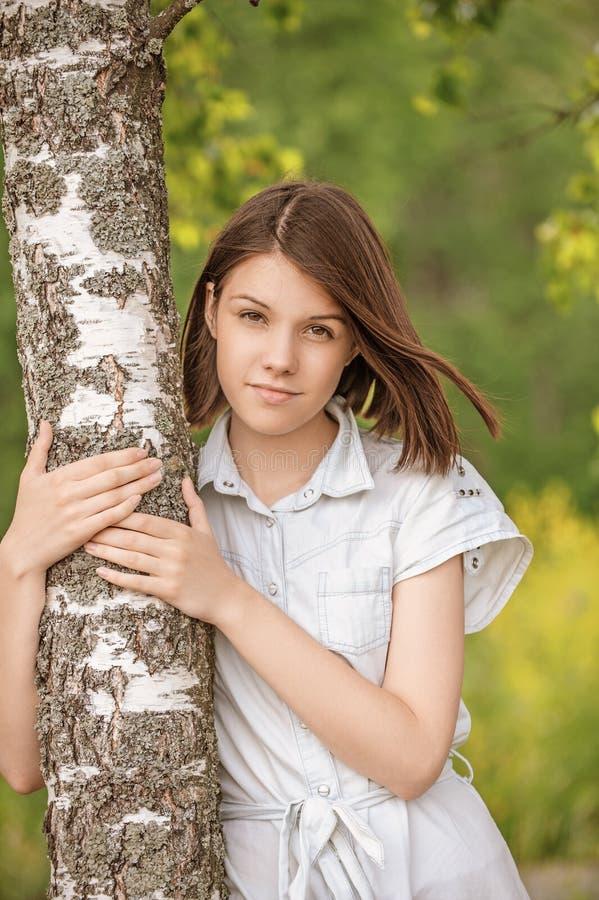 Портрет молодого темн-с волосами дерева березы обнимать женщины стоковые изображения