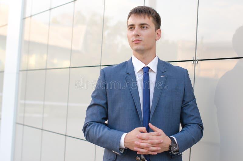 Портрет молодого успешного экономиста человека стоя в современном офисе внутреннем, уверенно мужчина одел в роскошное корпоративн стоковое изображение