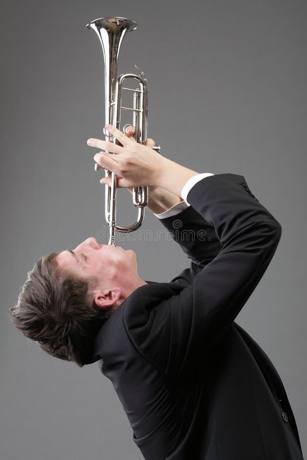 Портрет молодого человека играя его труба стоковое изображение rf