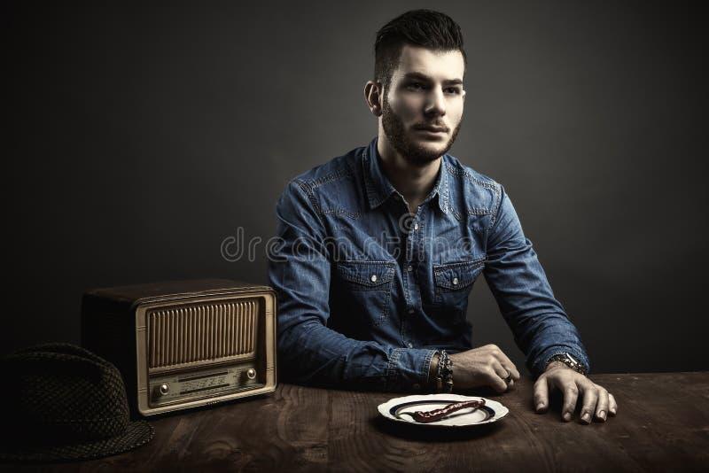 Портрет молодого человека сидя на таблице, винтажном стиле стоковые изображения rf