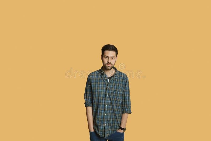 Портрет молодого человека стоя с руками в карманн над покрашенной предпосылкой стоковое фото