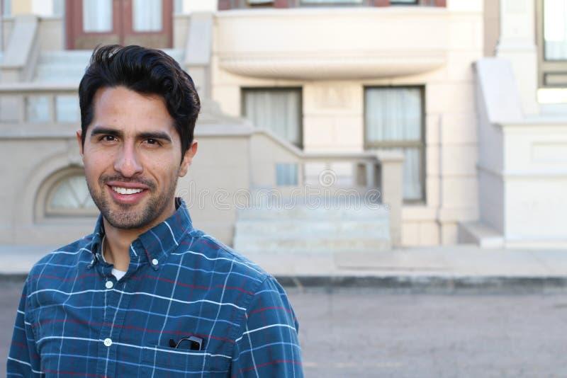 Портрет молодого человека усмехаясь с городским космосом предпосылки и экземпляра стоковые фото