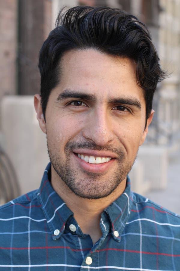 Портрет молодого человека усмехаясь с городской предпосылкой стоковая фотография