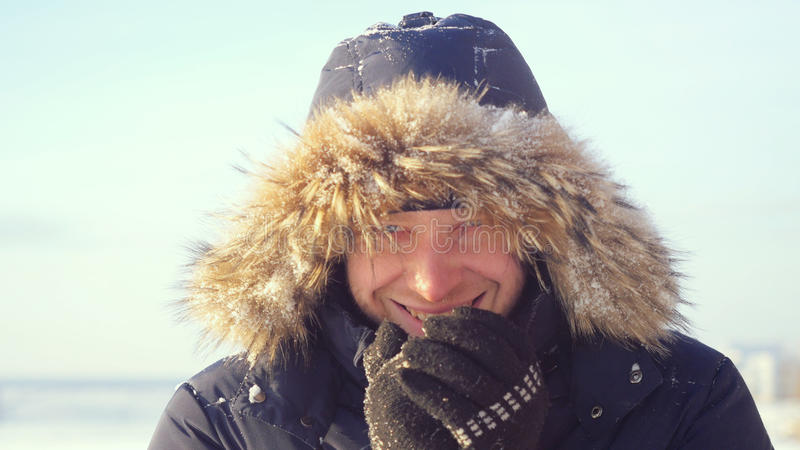 Портрет молодого человека улыбок outdoors замерзая смотреть в камеру нагревает его руки в зиме стоковые изображения rf