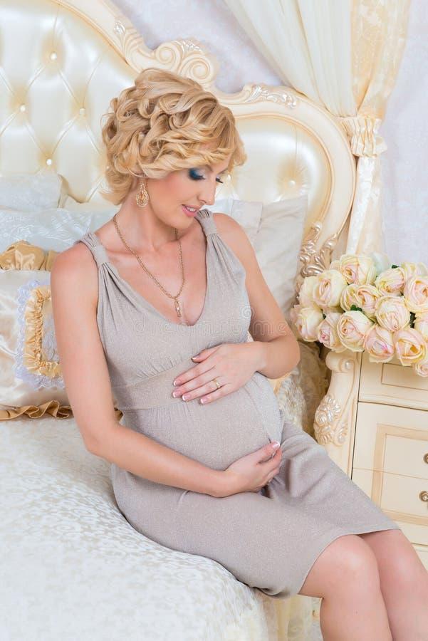 Портрет молодой беременной женщины касаясь ее животу при руки сидя на кровати в современном интерьере стоковое фото