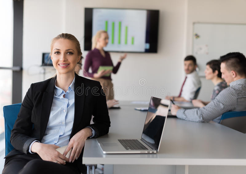 Портрет молодой бизнес-леди на офисе с командой на встрече стоковые изображения