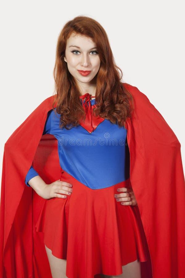 Портрет молодой женщины в костюме супергероя с руками на бедрах против серой предпосылки стоковые изображения