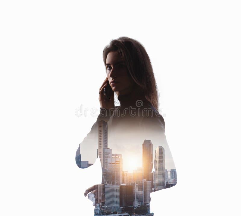 Портрет молодой женщины держа ее smartphone в руки Белая изолированная предпосылка стоковая фотография