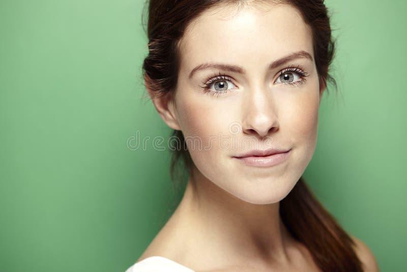 Портрет молодой женщины, против зеленой предпосылки стоковое фото