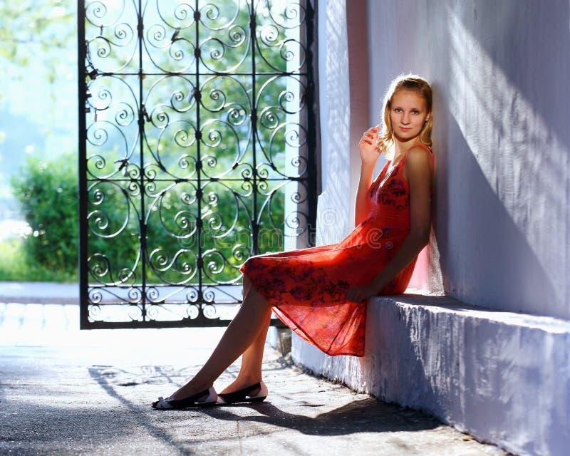 Портрет молодой женщины сидя около строба стоковые фотографии rf