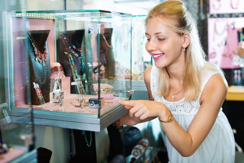 Портрет молодой женщины стоя рядом с стеклянными витринами стоковое изображение