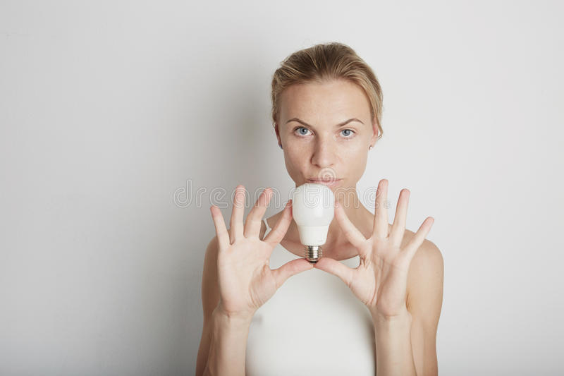 Портрет молодой женщины с белыми наушниками и электрическим светом с пустой предпосылкой стоковые фотографии rf