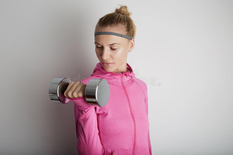 Портрет молодой женщины фитнеса милой нося розовые спорт одевает Свежая здоровая стильная девушка спорта используя запонки для ма стоковое фото rf