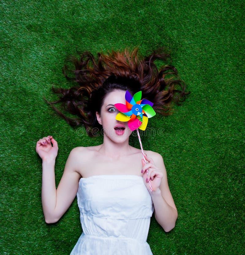 Портрет молодой женщины redhead при pinwheel лежа вниз на gr стоковое фото rf