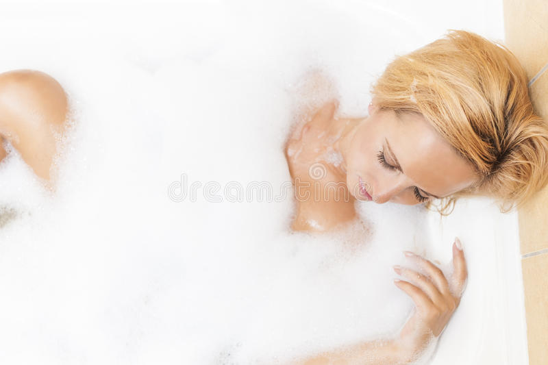 Портрет молодой кавказский белокурый женский ослаблять в ванне стоковые фотографии rf