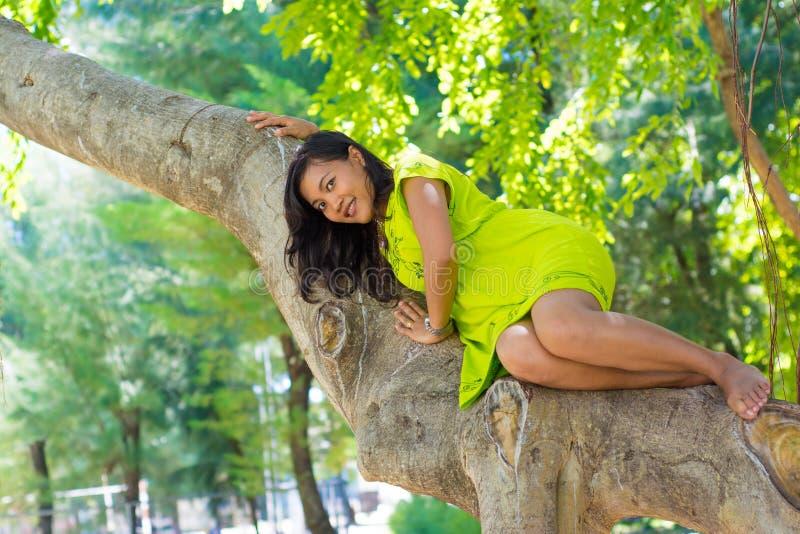Портрет молодой красивой азиатской девушки кладя на баньян и усмехаться стоковое фото rf