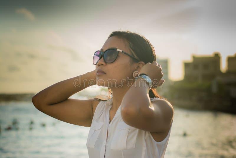 Портрет молодой красивой азиатской женщины в солнечных очках исправляя ее волосы стоковые изображения rf