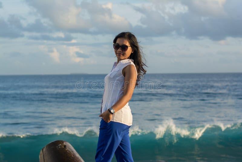Портрет молодой красивой азиатской женщины в солнечных очках на пляже города во время времени захода солнца смотря назад стоковая фотография