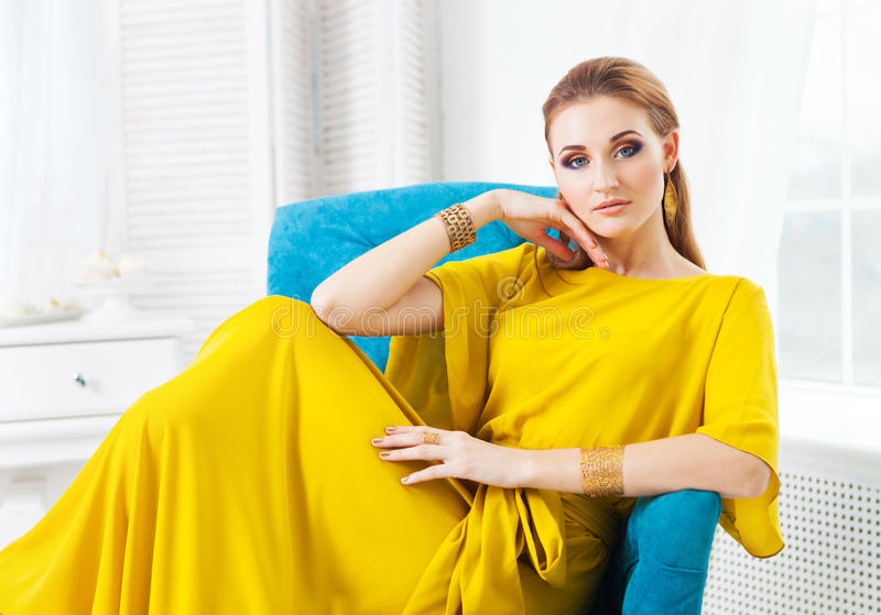 Портрет молодой красивой девушки нося длинное желтое платье стоковое фото