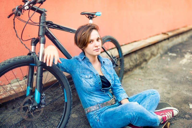 Портрет молодой красивой женщины брюнет нося обмундирование стильного лета битника sportive, городской образ жизни Усмехаться и h стоковая фотография
