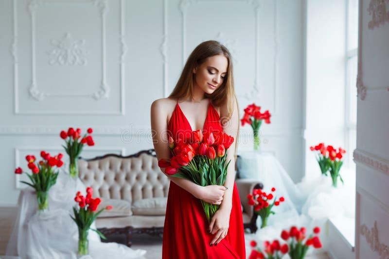 Портрет молодой красивой женщины в красном платье с тюльпанами в роскошном интерьере стоковая фотография rf