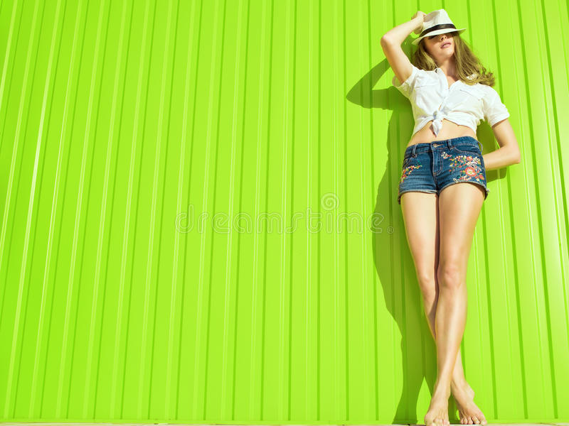 Портрет молодой красивой длинн-шагающей модели в белизне связал вверх рубашку, шорты джинсов с орнаментом цветка и Панаму стоковое фото rf