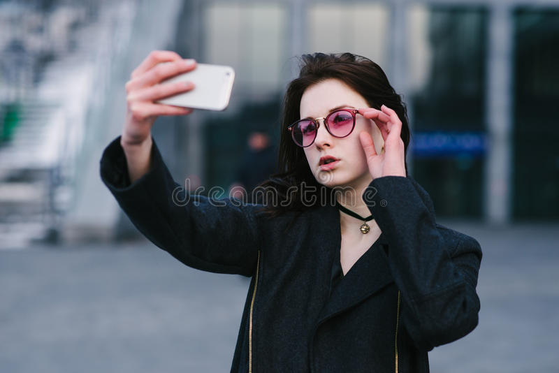 Портрет молодой красивой стильной девушки в розовых стеклах битника будучи сфотографированным на на вашем smartphone стоковые изображения