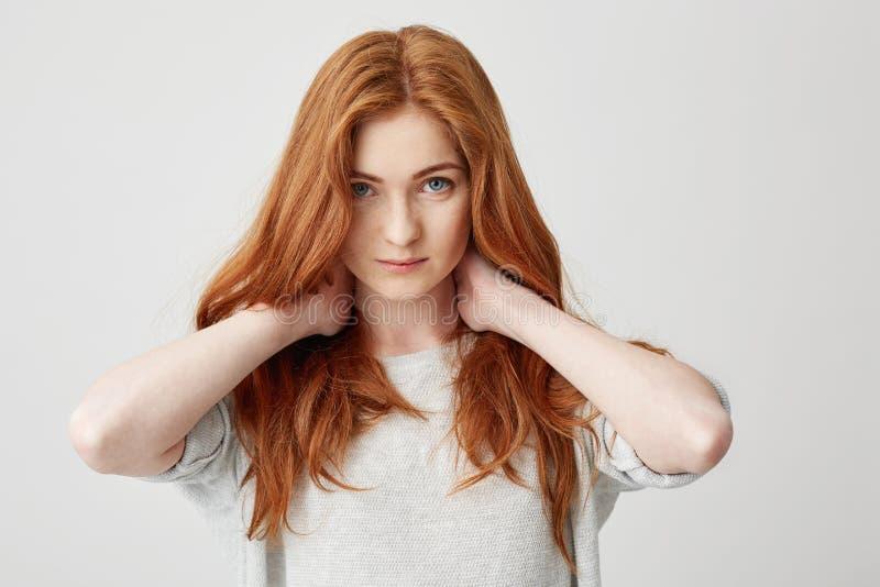 Портрет молодой милой девушки redhead смотря шею камеры касающую над белой предпосылкой стоковое фото rf