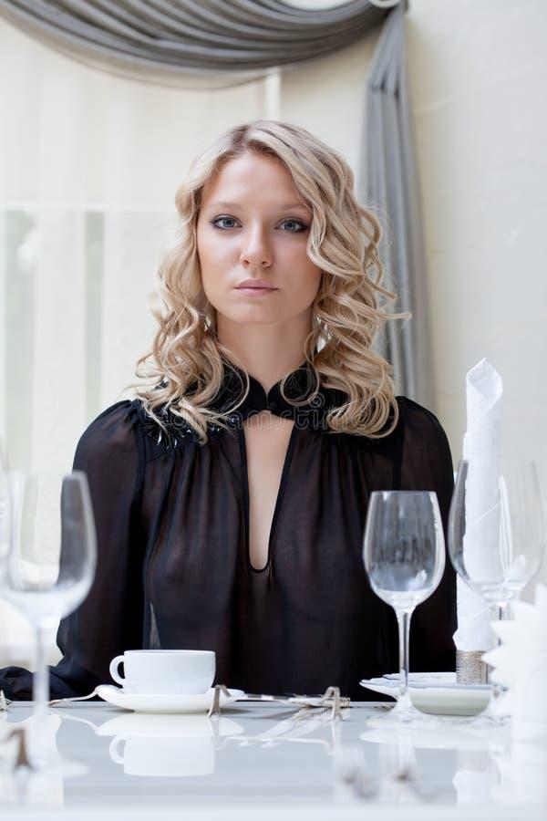 Портрет молодой привлекательной девушки сидя на таблице стоковое изображение rf
