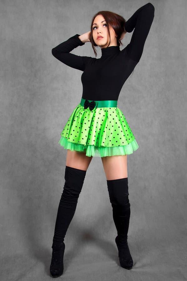 Портрет молодой привлекательной женщины в яркой ой-зелен юбке стоковое изображение