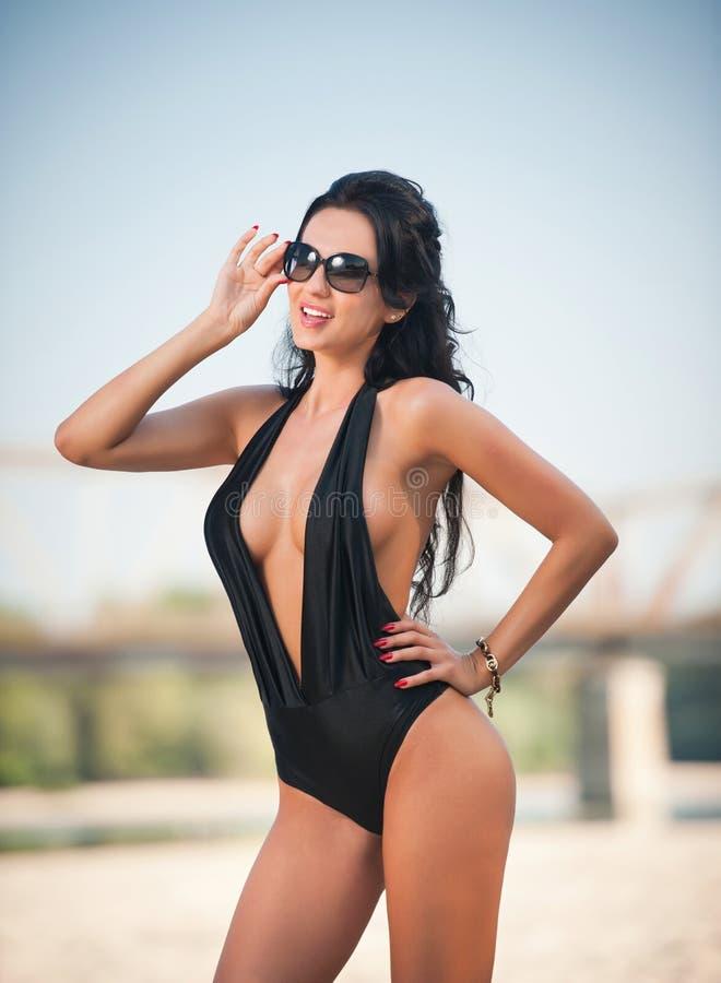 Портрет молодой сексуальной девушки брюнет в черном с большим вырезом купальнике представляя на пляже с мостом в предпосылке Чувс стоковые фотографии rf