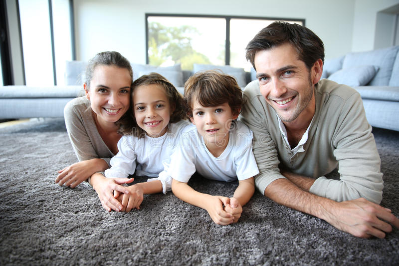Портрет молодой семьи дома лежа на мягком ковре стоковые фото