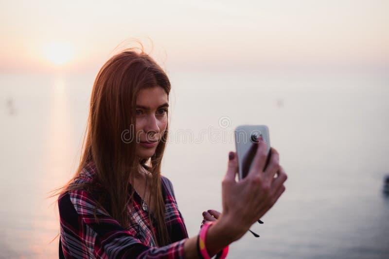 Портрет молодой счастливой женщины в рубашке битника стоя перед живописным видом на море, принимая selfie с заходом солнца или стоковое фото