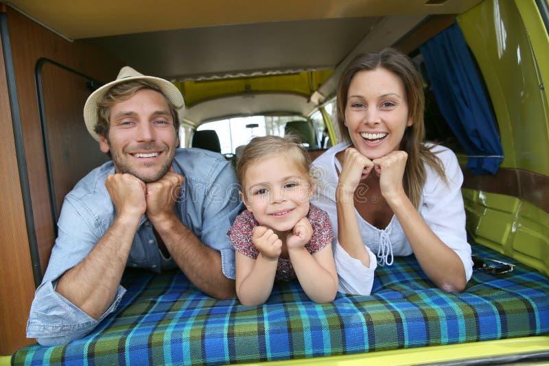 Портрет молодой счастливой семьи в располагаясь лагерем автомобиле стоковое фото