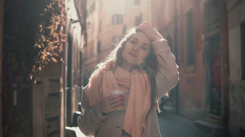Портрет молодой усмехаясь женщины смотря камеру Счастливая привлекательная девушка стоя в улице утра, делая вверх по волосам стоковое фото